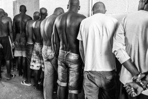 quando a liberdade e excecao - Chegando na unidade, presos tem os cabelos cortados e aguardam algemados uns nos outros no Pedro Melo